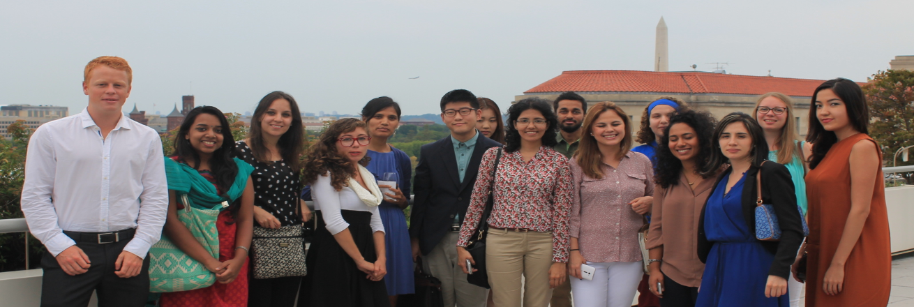 International students on balcony with DC skyline in the background.