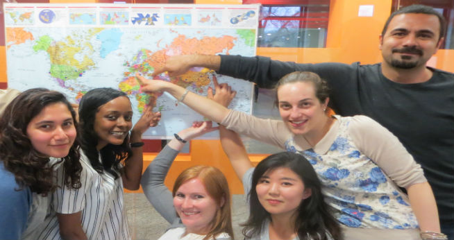 International students pointing at a map