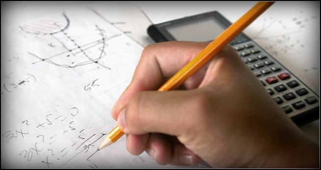 Student holding a pencil in hand doing math with a calculator