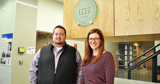 Chris Moody and Megan Litke pose under the LEED certification decal at the Cassell Hall LEED certification event.