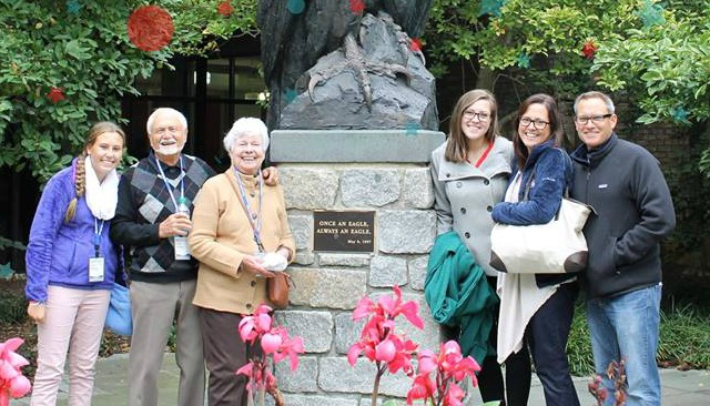 Six family members standing with the American University Eagle statue.