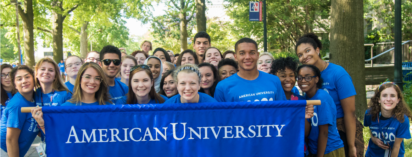 "Group of diverse college students all wearing blue ""Class of 2020"" t-shirts. The students in the front are holding a banner that says ""American University"""