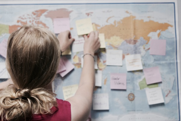 girl sticks sticky-note on world map for activity