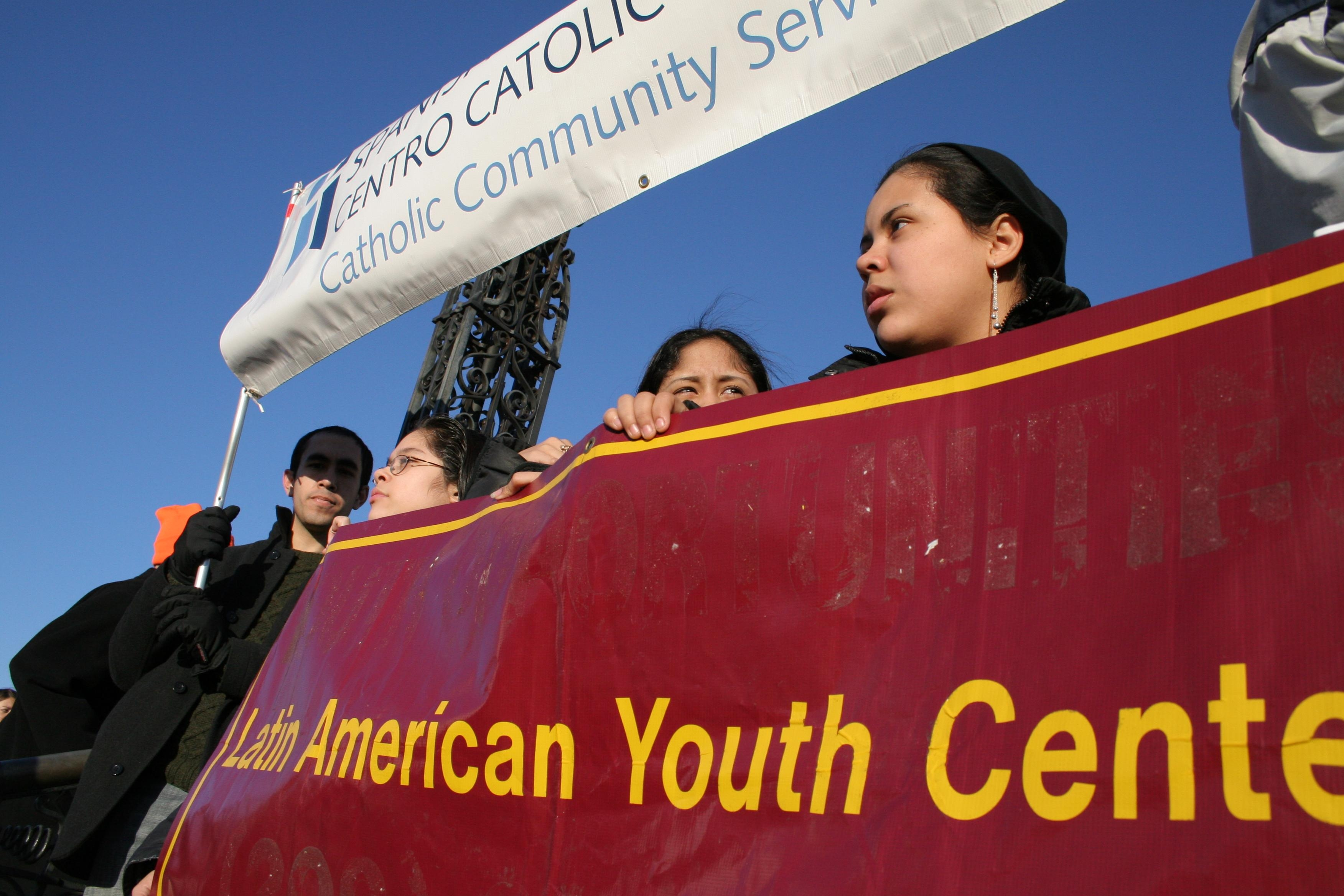 "students holding a banner saying, ""Latin American Youth Center,"" at a march"