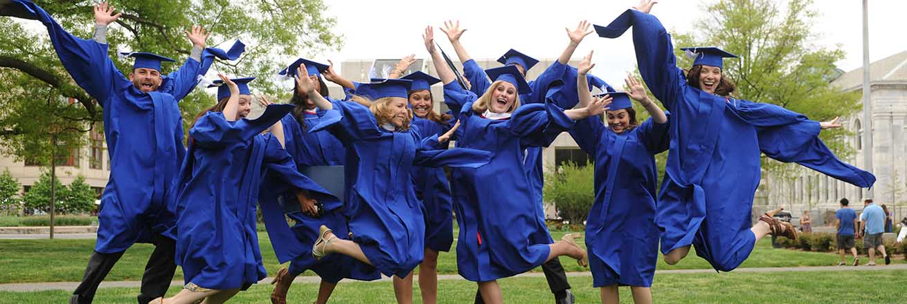 American University graduates leap in celebration on the Quad