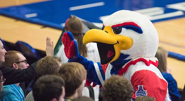 Clawed the Eagle high-fiving students