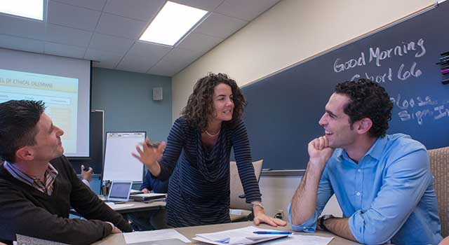 Graduate students confer during class