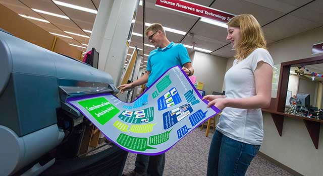 Students using the University Library's large format printer
