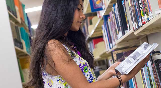 American University student perusing the shelves at Bender Library