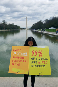 Alexis holding protest signs during the Freedom Walk fundraiser on the National Mall