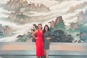 Jessica poses in front of a mural with fellow student at the Chinese Embassy