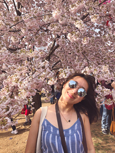 Hyeseung Jin poses in front of a cherry blossom tree that is ample with flower petals and buds.