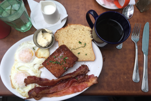Breakfast food: eggs, bacon, hashbrowns, toast, and coffee