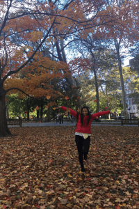 Alexis throwing fall leaves