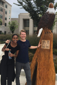 Mahalet and friend by the American eagle statue on campus