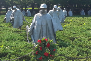 Korean War Memorial with statues of soldiers; a red rose wreath in front