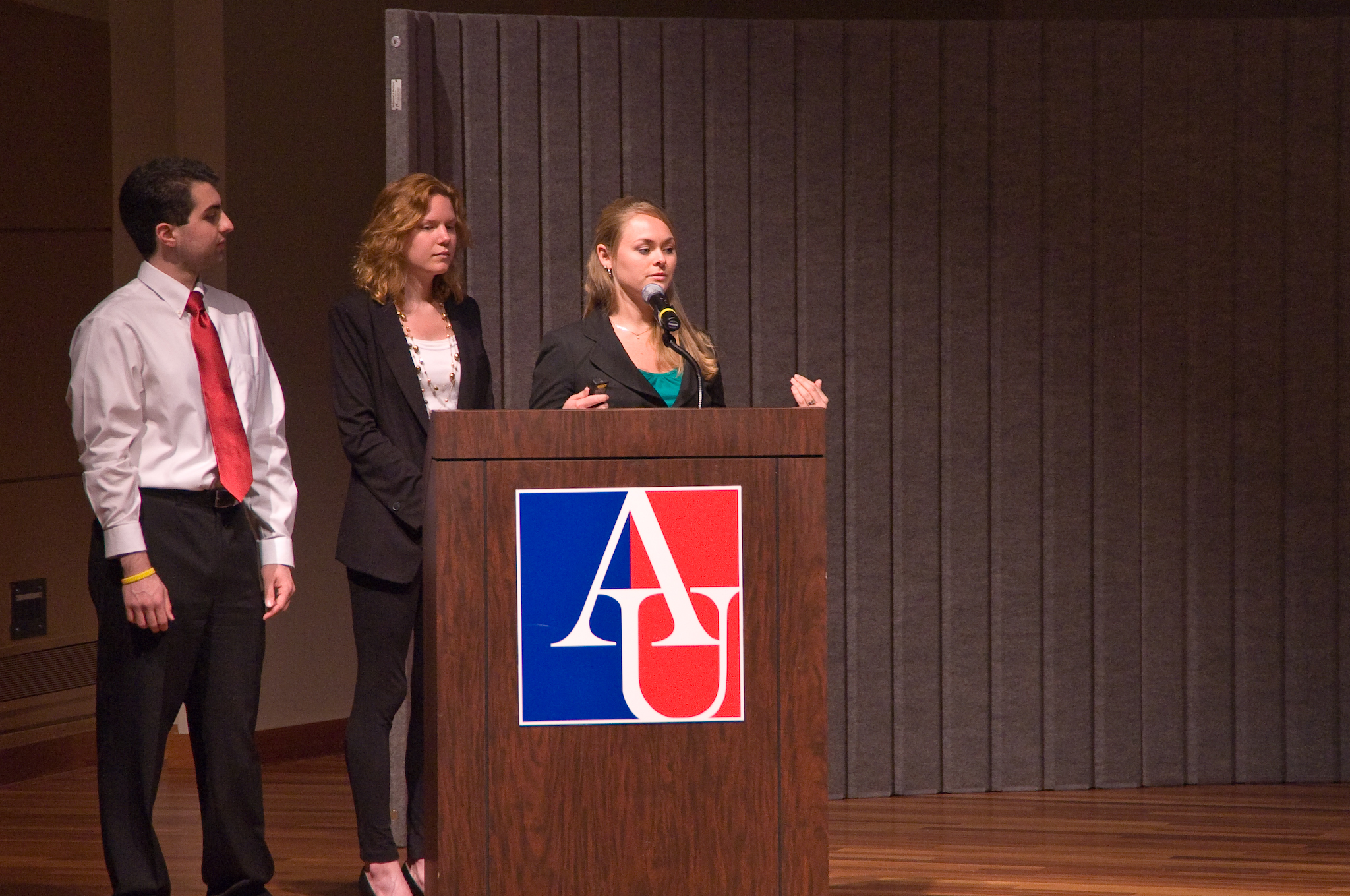 three students standing at podium with AU logo on the front.