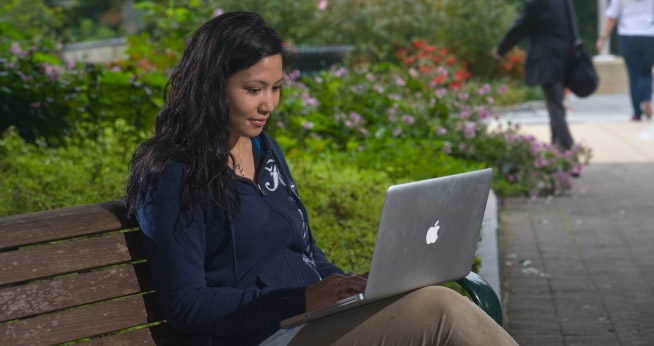 AU student using a laptop outdoors on campus