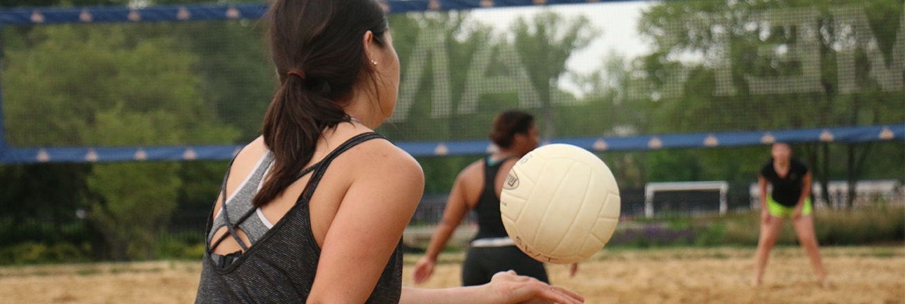 females playing sand volleyball