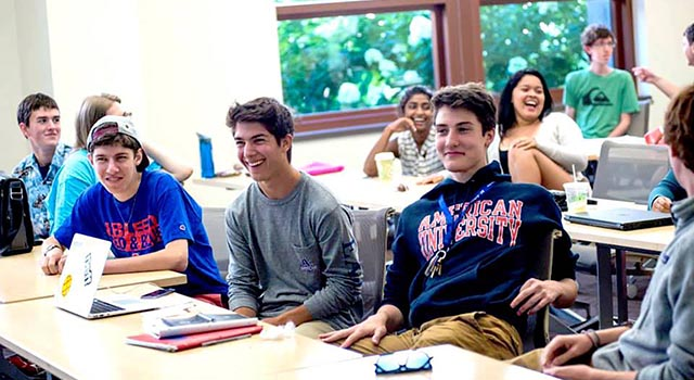 group of laughing students in an SIS classroom that participated in the Community of Scholars program