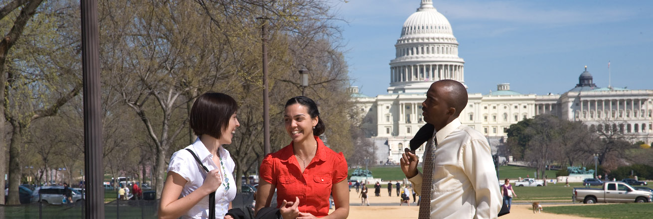 three students gather on the National Mall with the Capital building in the distance