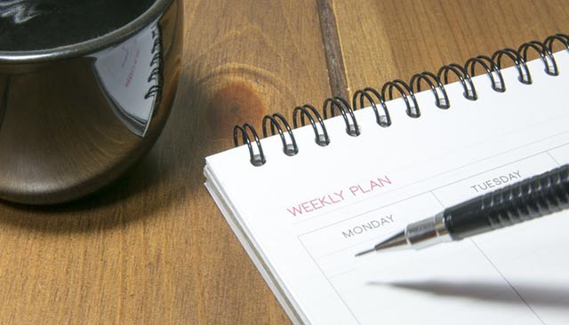 coffee mug with weekly planner and pen sitting on a table