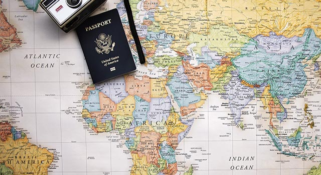 old film camera and US passport lay on top of a world map