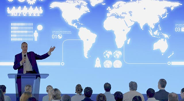 man giving presentation to group of people with world map infographic displayed behind him