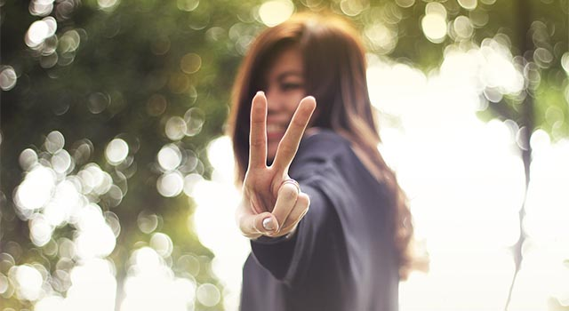 girl giving peace sign