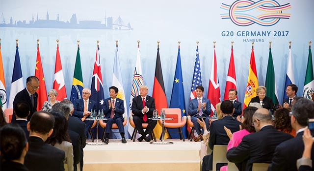 world leaders sit on a stage with multiple country flags behind them at the 2017 G20 Summit