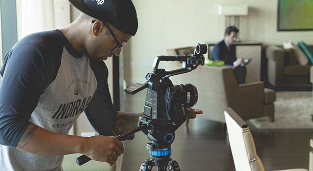 a guy sets up a production camera to film a location