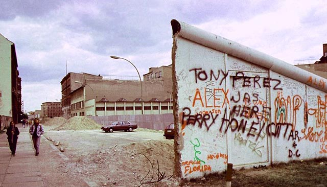 A partial section of the Berlin Wall stands, covered in graffiti.