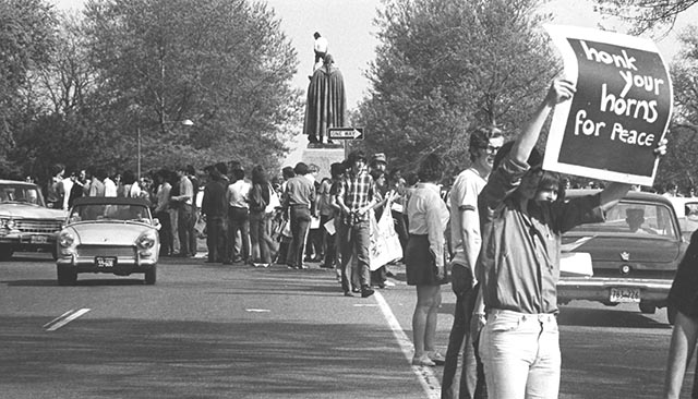"Students stop traffic in Ward Circle in protest of Vietnam War. One student holds a sign that reads ""Honk your horns for peace."""