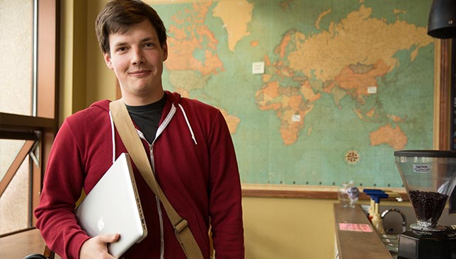 students stands with laptop in front of world map
