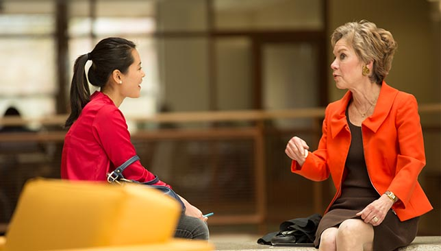 student has an informal conversation with an SIS faculty member