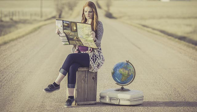 Girl sits on a suitcase reading a map with globe next to her