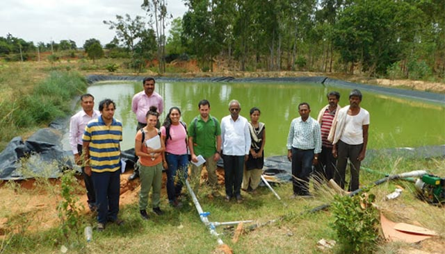 Students pose with their clients who they helped set up an irrigation system in a field