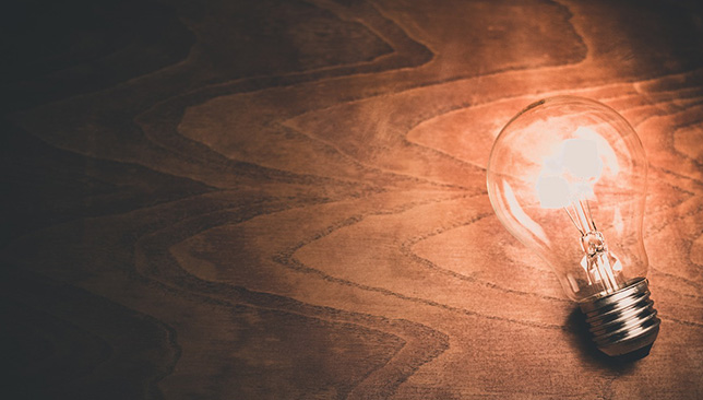 lightbulb lit up on wooden table