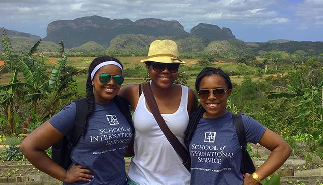 three girls with School of International Service shirts with hilly terrain
