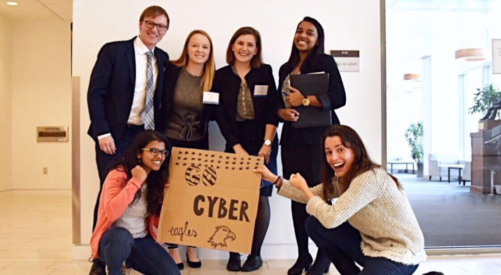 "Six members of an American University Cyber 912 team pose together with a sign that reads ""Go Cyber Eagles"""