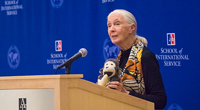Jane Goodall holds a plush monkey toy while delivering a lecture at a podium inside the Atrium at the School of International Service