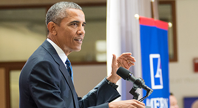 President Barack Obama delivers a speech at a lectern at the School of International Service.