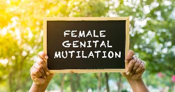 "Two hands hold up a chalkboard sign that reads ""Female Genital Mutilation"""