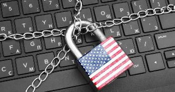 A padlock with an American flag design secures a computer keyboard, symbolizing national security.
