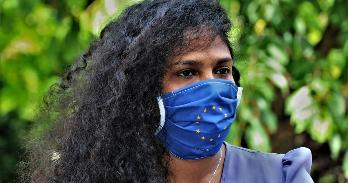 A woman wears a mask with a European flag design.