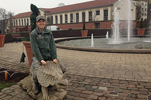 Harriett sits atop a stone triceratops sculpture in her military camoflauge