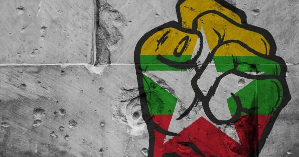 Painted fist on a concrete wall colored in the Myanmar flag.