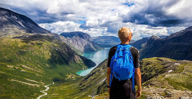man with backpack looks out over river winding between lush mountains in Norway