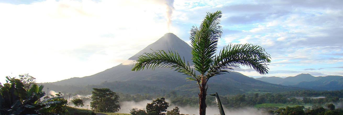 volcano in Costa Rica steams with palm trees and rainforest surrounding it