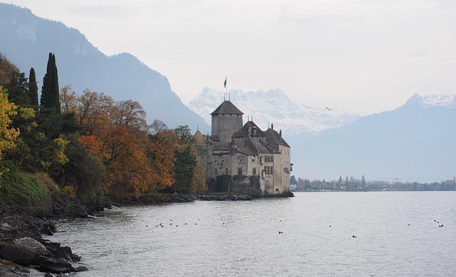 Chillon Castle on the banks of Lake Geneva with the snow-capped mountains behind it